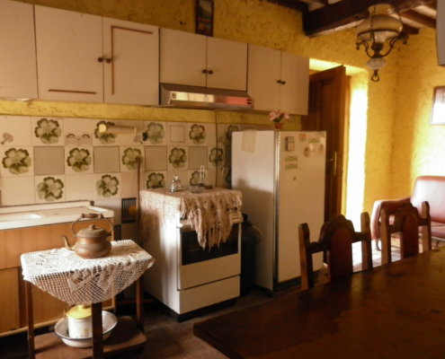 Traditional rustic kitchen in this property for sale with original tiles and dining area